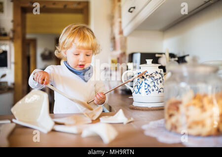 Toddler boy in dangerous situation at home. Child safety concept. - Stock Photo