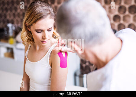 Senior male physiotherapist applying tape on a female patient. - Stock Photo