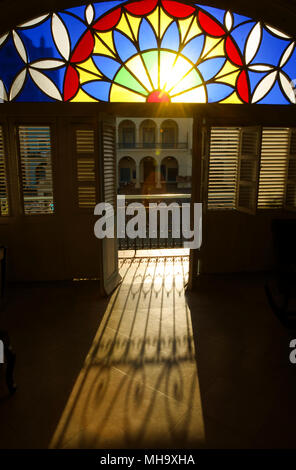 The morning sun shines through stained glass and an open door of a casa particular on Plaza Vieja in Havana, Cuba. - Stock Photo
