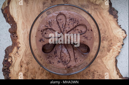 Glass bowl with chocolate mousse standing on an olive wood platter, decorated with chocolate shavings and curls. - Stock Photo