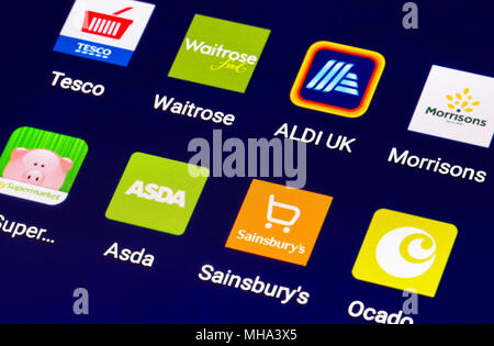 Icons on a tablet for online food shops in the UK. Grocery shopping online on a mobile device. Modern Internet shopping shortcuts for grocery stores.. - Stock Photo