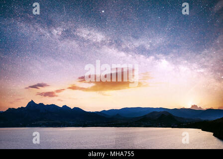 magnificent panorama of sunrise over the sea. Vibrant night sky with stars and nebula and galaxy. Deep sky astrophoto - Stock Photo
