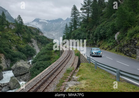 Volvo oldtimer car driving on a mountain pass in the Swiss Alps near Gletsch, Switzerland. - Stock Photo