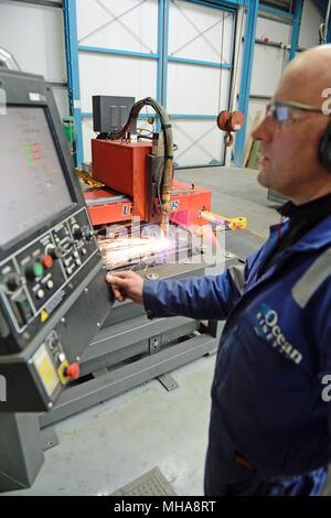 Man working on a metal plasma cutting machine in an engineering workshop - Stock Photo