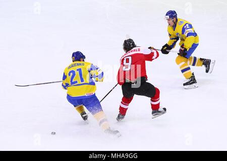 KYIV, UKRAINE - APRIL 25, 2017: Alex RAUCHENWALD of Austria (C) fights for a puck with Denys ISAYENKO (L) and Artem GNIDENKO of Ukraine during their I - Stock Photo