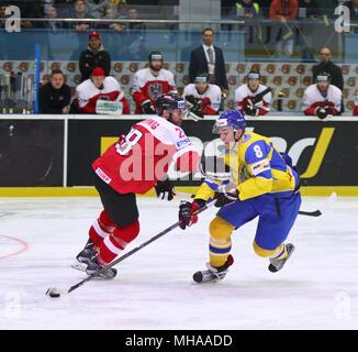 KYIV, UKRAINE - APRIL 25, 2017: Martin SCHUMNIG of Austria (L) fights for a puck with Vitali LYALKA of Ukraine during their IIHF 2017 Ice Hockey World - Stock Photo
