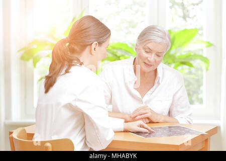 Smiling middle aged doctor showing her relieved senior patient the current mri of her head - Stock Photo