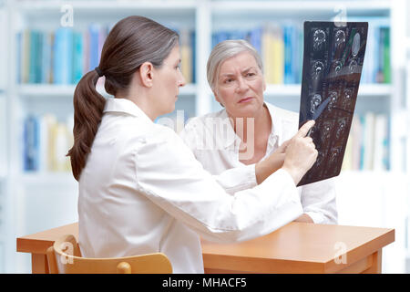 Female middle aged doctor discussing with her senior stroke patient ct-scan images of her brain - Stock Photo