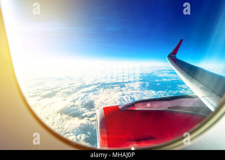 Flying with an airplane, view of the wings, engine, sky and the clouds through the aircraft window during flight on a nice sunny day - Stock Photo