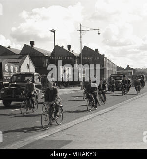 1950s, historical picture showing employees on their bikes leaving en mass from the Pressed Steel car bodies manufacturing plant at Cowley, Oxford. This giant industrial complex covering more than half the size of London's Hyde Park employed 12,000 workers at this time and were the largest manufacturers of mass-produced car bodies in Britain. Such was the growth of the motorcar over the next decade, that by 1965 Pressed Steel employed some 26,000 people. - Stock Photo