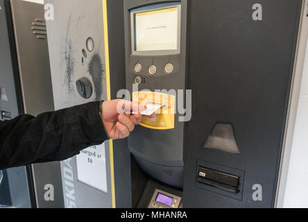 Man paying for parking at a parking machine in a carpark - Stock Photo