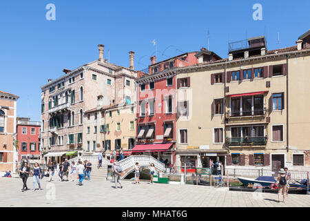 Colorful buildings and bridge on Campo dei Frari, San Polo, Venice, Veneto, Italy with tourists in spring - Stock Photo