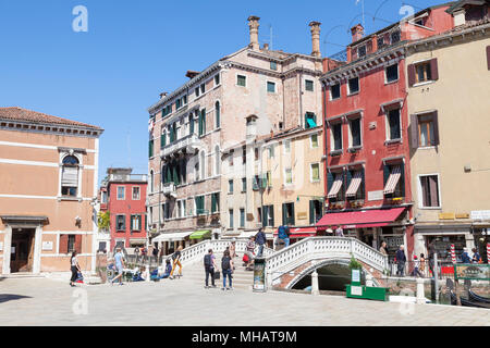 Colorful buildings and bridge on Campo dei Frari, San Polo, Venice, Veneto, Italy with a few tourists in early spring - Stock Photo