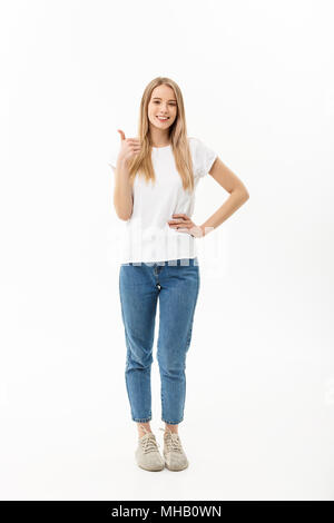 Lifestyle Concept: Happy smiling young woman in jeans looking at the camera giving a thumbs up of success and approval isolated on white - Stock Photo