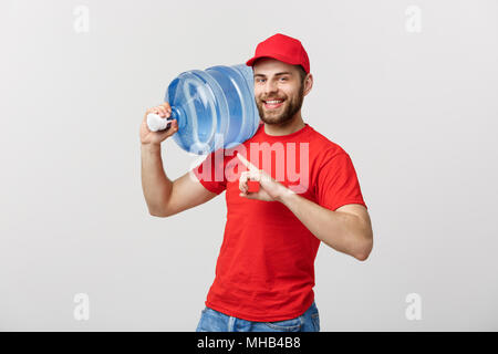 Portrait smiling bottled water delivery courier in red t-shirt and cap carrying tank of fresh drink and pointing finger isolated over white background. - Stock Photo