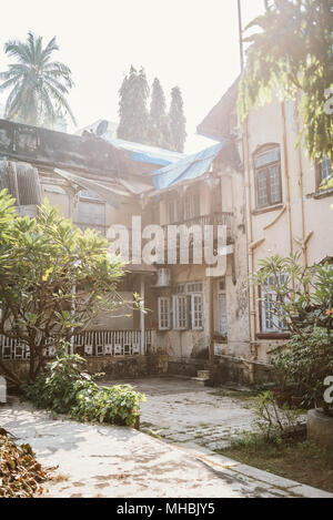 Dilapidated Colonial building complex on a sunny day in Mumbai, India surrounded by trees - Stock Photo
