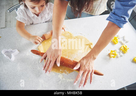 Happy family preparation holiday food concept. Family cooking Christmas cookies. Hands of mother and daughter preparing the dough on the table. Happy family in making cookies at home - Stock Photo