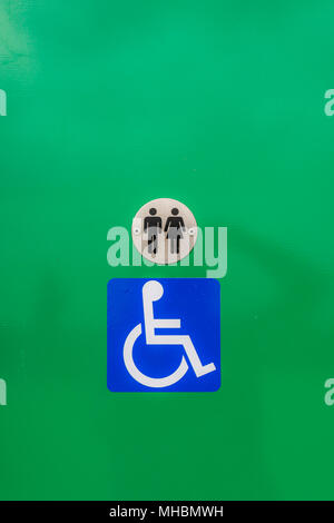 Disabled toilet sign, against a green background - Stock Photo