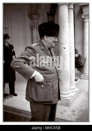 Winston Churchill smoking his ever present signature cigar at the entrance of the Livadia Palace during the Yalta Conference in 1945. British Prime Minister Winston Churchill (1874-1965) at the entrance to the Livadia Palace during the Yalta Conference of the leaders of the countries of the anti-Hitler coalition. - Stock Photo
