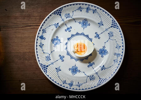 Halved hard boiled egg on a blue and white plate - Stock Photo