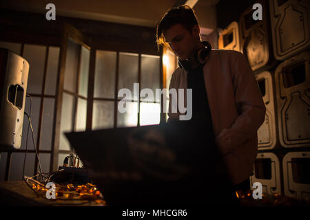 Portrait of trendy young DJ playing music using mixer and looking at laptop screen in  night club party, copy space - Stock Photo