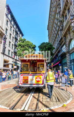 SAN FRANCISCO - APR 2, 2018: A worker rotates a cable car at the Powell and Market street turntable to pick up a crowd of passengers. A San Francisco  - Stock Photo