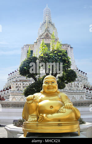Golden Buddha in front of Wat Arun, the beautiful white Buddhist temple in Bangkok, Thailand. - Stock Photo