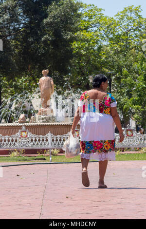 Mexican mom goes back home from the market. Her typical dress called 'huipil' is also present in the fountain statue. Bright white and colorful embroi - Stock Photo