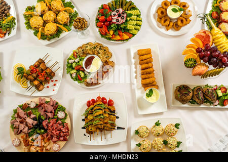 Different snacks for eating on holiday in white plates on white background. Kitchen, menu, food concept . delicious dish - Stock Photo