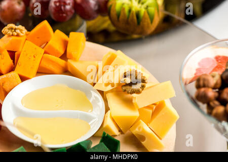Pieces of cheese of different varieties with honey - Stock Photo