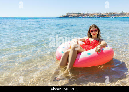Beautiful young woman relaxing on inflatable donut in sea. - Stock Photo