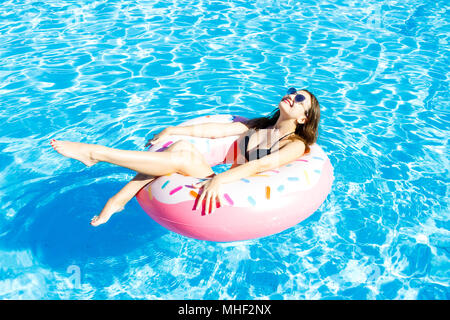 Beautiful young woman on inflatable donut in swimming pool. - Stock Photo