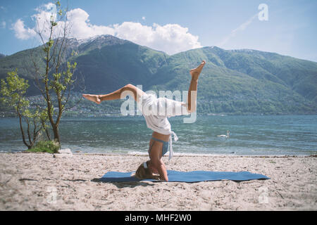 Young woman exercising yoga by the lake and mountains, shot in Ticino Canton, Switzerland, Europe. People relaxation wellbeing concept - Stock Photo