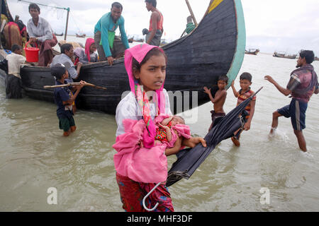Rohingya refugees walk to the shore after crossing the Bangladesh-Myanmar border by boat through the Bay of Bengal in Shah Porir Dwip. Teknaf, Cox's B - Stock Photo