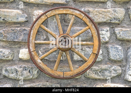 Far west wagon wheel isolated on wall - Stock Photo