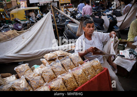 Reading a newspaper in the crowded streets in the old city of Ahmedabad, Manek Chowk. Gujarat, India. - Stock Photo