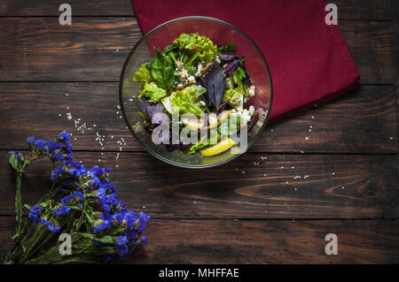 Top view of freshly harvested lettuce, lemon, blue cheese, pearand flowers on an old wood table. - Stock Photo