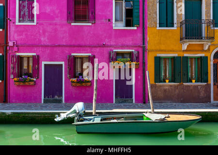 Boat on narrow canal in front of colorful houses of Burano, Italy. - Stock Photo