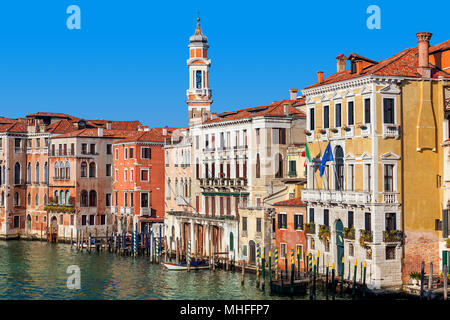 View of colorful buildings along Grand canal under blue sky in Venice, Italy. - Stock Photo