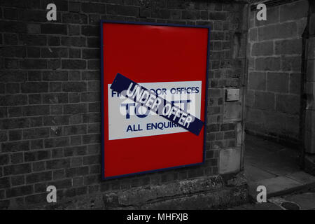 To let under offer sign for an office on a brick wall with selective color - Stock Photo