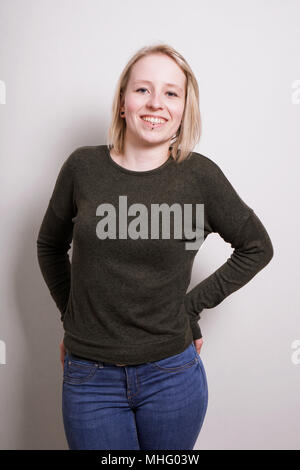 young blond millennial woman smiling, three quarter length real people portrait - Stock Photo
