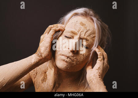 woman covered in dry cracked clay mud mask holding her head in pain - Stock Photo