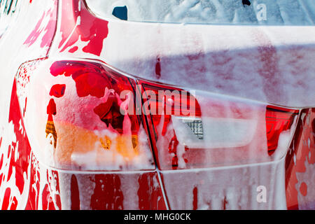 Back view of red compact SUV car with sport and modern design washing with soap. Car covered with white foam - Stock Photo