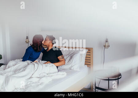 Romantic couple kissing in bed. Interracial man and woman sitting on bed and kissing each other. - Stock Photo