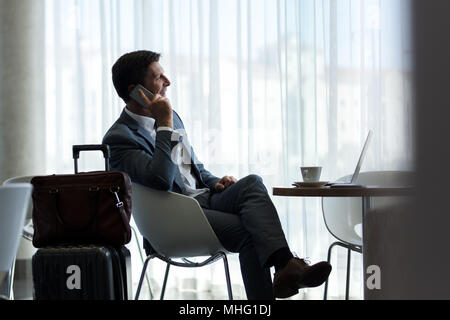 Business man sitting at airport lounge and talking on mobile phone. Male business traveler sitting at airport waiting area with suitcase waiting for t - Stock Photo