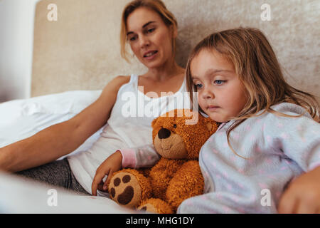 Little girl reading an interest book sitting on the bed with her mother. Mother and daughter reading a book in bed. - Stock Photo