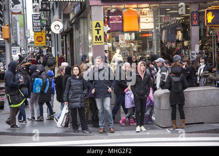 Mostly tourists with shopping bags wait to cross 42nd Street in the Times Square district in midtown Manhattan, NYC. on a cool spring day. - Stock Photo