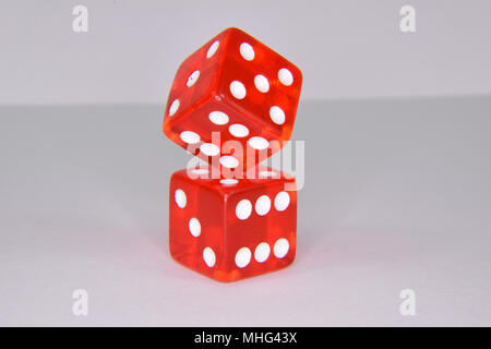 Stacked and balancing red luminescent casino gambling dice - isolated - Stock Photo