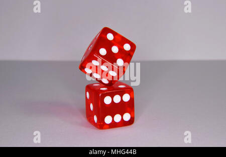 Balancing red luminescent casino gambling dice - Stock Photo
