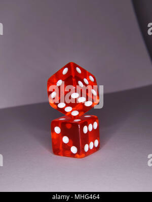 Balancing red luminescent casino gambling dice - vibrant colors and box composition - Stock Photo